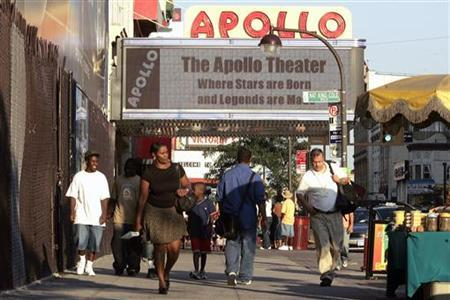 Pedestrians make their way along 125th Street near the Apollo Theater